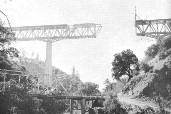 The original Yankee Hill bridge–shown here in 1962 during construction of the Highway 70 bridge overhead, a black-and-white photograph published a year later in Bill Talbitzer's book Lost Under the Feather–was two lanes wide if you had a vivid imagination, just like the two meandering ribbons of Nelson Bar Road that it tied together. That's me in the middle in the second photo (below), standing on the same bridge in 1956 with my brothers while on a Falstaff beer run. Already I seem to be commenting on the scenery.